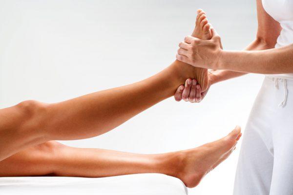 Osteopathin massiert den Fuß einer Frau.