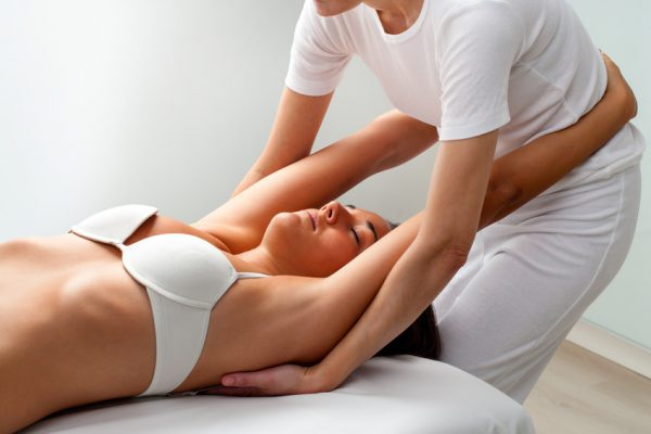 Eine junge Frau bekommt eine osteopathische Behandlung.